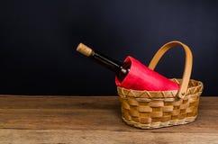 бутылки красного вина на плетеной корзине на деревянном столе Стоковые Фотографии RF