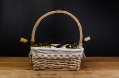 бутылки красного вина на плетеной корзине на деревянном столе Стоковые Изображения