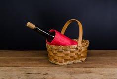 бутылки красного вина на плетеной корзине на деревянном столе Стоковые Фото