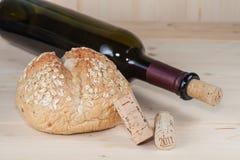 Бутылки красного вина с пробочками и хлеб на деревянном Стоковые Фотографии RF