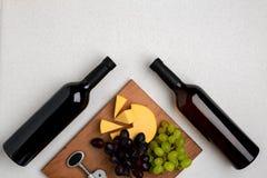 Бутылки красного и белого вина на белой предпосылке от взгляд сверху Стоковые Изображения