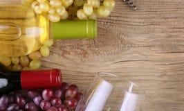 Бутылки красного и белого вина на старой древесине Стоковые Изображения RF