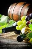 Бутылки красного и белого вина с свежей виноградиной Стоковое фото RF