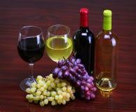 Бутылки красного и белого вина с свежими виноградинами. Стекла вина Стоковое Изображение