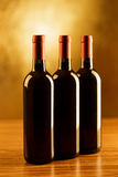 3 бутылки красных вина на деревянном столе и золотой предпосылке Стоковое фото RF