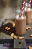 2 бутылки миндалины шоколада доят с бумажными соломами Стоковые Фото
