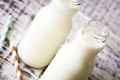 2 бутылки молока при striped соломы стоя на старой таблице Стоковые Изображения