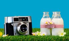 3 бутылки молока с камерой в траве Стоковое Фото