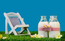 3 бутылки молока с креслом для отдыха в траве Стоковые Изображения