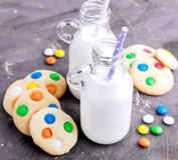 2 бутылки молока с соломами и печеньями Стоковое Фото
