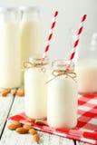2 бутылки молока с striped соломами и миндалинами на белой деревянной предпосылке Стоковая Фотография RF