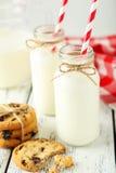 2 бутылки молока с striped соломами и печеньями на белой деревянной предпосылке Стоковые Фотографии RF