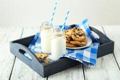 2 бутылки молока с striped соломами и плитой печений на белой деревянной предпосылке Стоковое Изображение