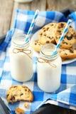 2 бутылки молока с striped соломами и плитой печений на серой деревянной предпосылке Стоковые Изображения