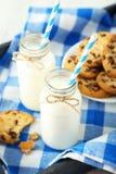 2 бутылки молока с striped соломами и плитой печений Стоковое Изображение