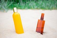 Бутылки лосьона и брызга Suntan на песчаном пляже Стоковые Изображения RF