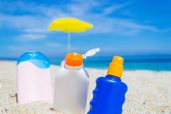 Бутылки лосьона Suntan на песке Стоковые Фотографии RF