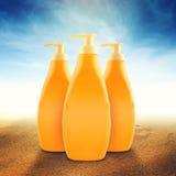 Бутылки лосьона Suntan на солнечном пляже Стоковая Фотография