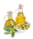 Бутылки оливкового масла и зеленых оливок с листьями Стоковые Изображения RF