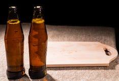 Бутылки пива и деревянной разделочной доски на таблице Стоковое Изображение