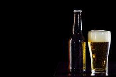 Бутылки пива и стекла получая холодный на черной предпосылке Стоковое Фото
