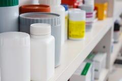 Бутылки пилюлек аранжировали на полке на аптеке Стоковые Фото