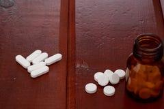 Бутылки пилюлек Брайна и куча белых пилюлек Стоковые Фотографии RF
