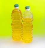 2 бутылки подсолнечного масла на желтой предпосылке Стоковая Фотография RF