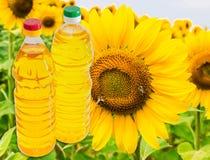 2 бутылки подсолнечного масла на предпосылке солнцецвета Стоковое Изображение