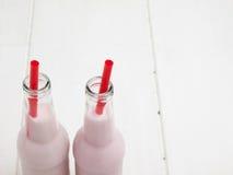 2 бутылки розового milkshake с соломами Стоковые Фото