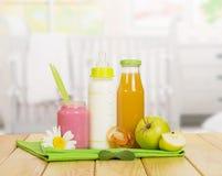 Бутылки с молоком и соком, пюрем плодоовощ на кухне предпосылки Стоковая Фотография