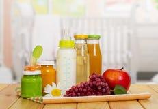 Бутылки с молоком, соком и пюрем, яблоком, виноградинами на кухне Стоковые Изображения RF