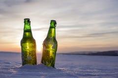 2 бутылки холодного пива на заходе солнца Стоковые Изображения