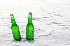 2 бутылки холодного пива на снеге на заходе солнца Стоковые Фотографии RF