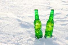 2 бутылки холодного пива на снеге на заходе солнца Стоковое фото RF