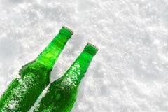 2 бутылки холодного пива на снеге на заходе солнца Стоковые Фото
