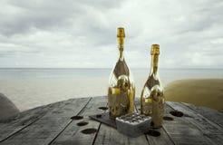 2 бутылки шампанского на старом деревянном столе с местами pouf для романтичного обедающего для copules медового месяца на тропич Стоковые Изображения