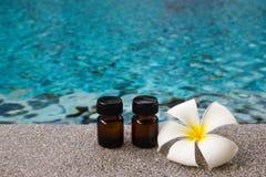 2 бутылки эфирного масла ароматности и цветка frangipani или plumeria на предпосылке бассейна Стоковое Изображение