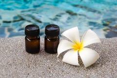 2 бутылки эфирного масла ароматности и цветка frangipani на предпосылке бассейна Стоковое фото RF