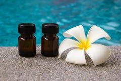 Бутылки эфирного масла ароматности и цветка frangipani на предпосылке бассейна Стоковые Изображения RF