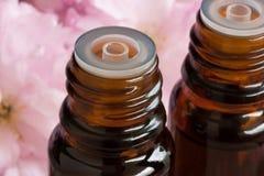 2 бутылки эфирного масла с розовыми цветениями на заднем плане Стоковое фото RF