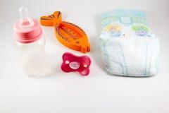 Бутылки, pacifiers, и пеленка младенца на белой предпосылке Стоковое Фото