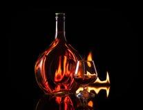 Бутылочное стекло конгяка в пламени пожара Стоковое Фото