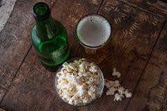 Бутылочное стекло холодного пива с попкорном на деревянном столе Стоковые Изображения