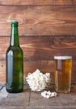 Бутылочное стекло холодного пива с попкорном на деревянном столе Стоковая Фотография RF