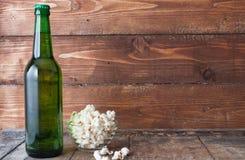 Бутылочное стекло холодного пива с попкорном на деревянном столе Стоковые Изображения RF