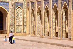 БУХАРА, УЗБЕКИСТАН - 9-ОЕ МАЯ 2011: Узбекский человек при его 2 дет идя в двор мечети Poy Kalon Стоковые Фото