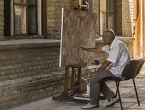 БУХАРА, УЗБЕКИСТАН - JULE 02, 2018: Старик рисует абстракцию с кистью стоковое изображение rf