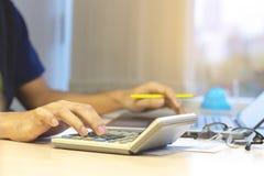 Бухгалтер бизнесмена используя калькулятор и ноутбук для calculati стоковые фото