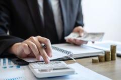 Бухгалтер бизнесмена считая деньги и делая примечания на отчете делая финансы и высчитать о цене вклада и стоковые фотографии rf